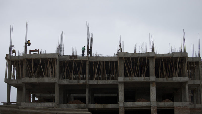 Men build a building in Gandhinagar, India, on Wednesday, Aug. 8, 2012. Photographer: Adeel Halim/Bloomberg